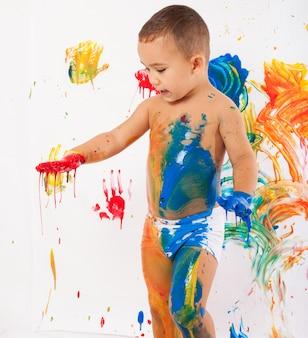 Niño divirtiéndose con pintura de diferentes colores