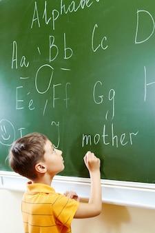 Niño escribiendo con una tiza en una pizarra