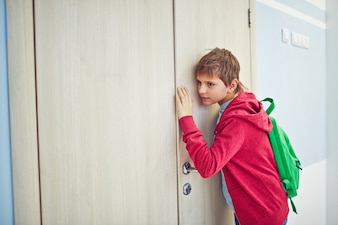 Niño escuchando detrás de la puerta