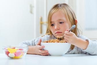 Niño hermoso que desayuna en el país.