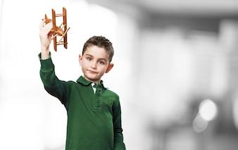 Niño jugando con un avión de madera