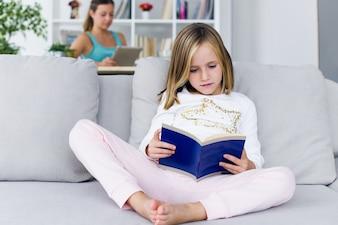 Niño leyendo un libro mientras su madre usando la tableta digital en h