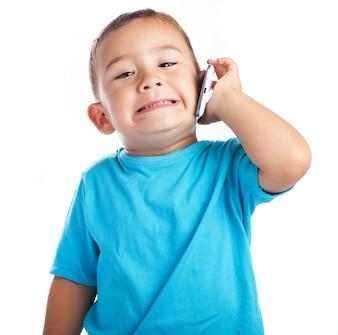 Niño pequeño con un teléfono en la oreja