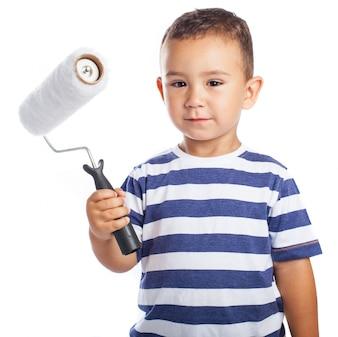 Niño pequeño con una brocha de pintura
