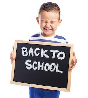 Niño pequeño llorando con una pizarra negra con el mensaje  back to school