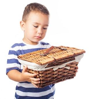 Niño pequeño mirando con pena una cesta de mimbre