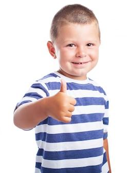 Niño pequeño sonriendo con un pulgar arriba