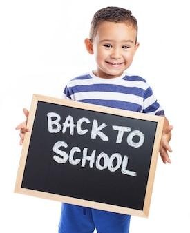 Niño pequeño sonriendo con una pizarra negra con el mensaje  back to school