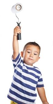 Niño pequeño sujetando en alto un rodillo de pintura