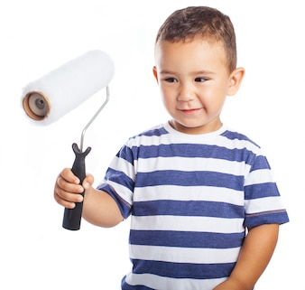Niño pequeño sujetando un rodillo de pintura