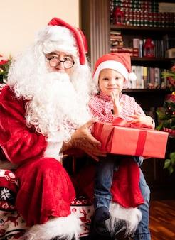 Niño sentado en las piernas de papa noel con un regalo