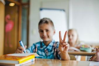 Niño, sentado, escuela, escritorio, gesticular