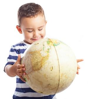 Niño sonriendo con un globo terráqueo