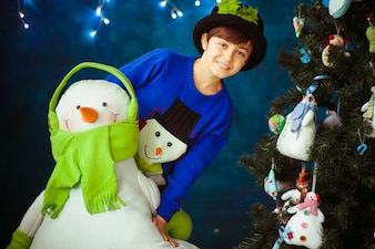 Niño sonriente abrazando un muñeco de nieve