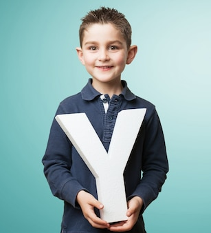 Niño sonriente sujetando la letra y