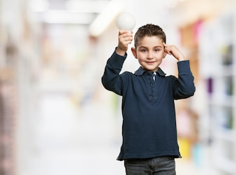 Niño sonriente sujetando una bombilla