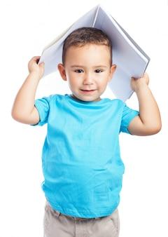 Niño usando una libreta como sombrero