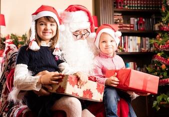 Niños adorables sentados en las piernas de papá noel en navidad