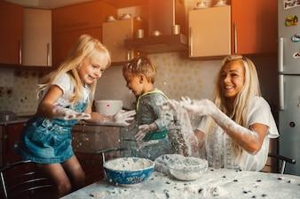 Niños cocinando con su madre y tirando harina