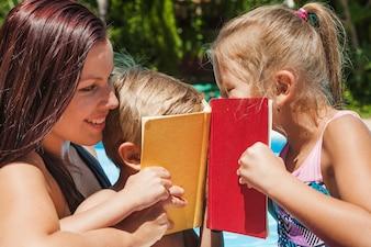 Niños cubriendo caras con libros