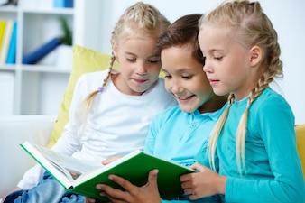 Niños emocionados leyendo un libro