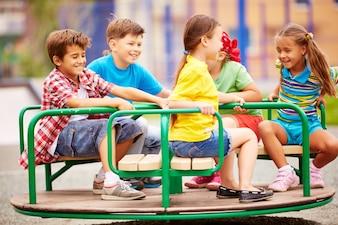 Niños jugando y riendo con el carrusel