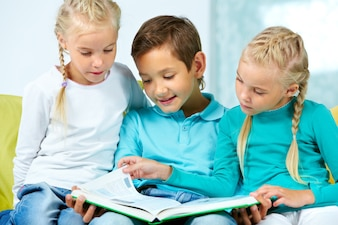 Niños sentados en el sofá leyendo