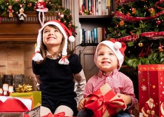 Niños sonriendo con regalos y sombreros de papa noel