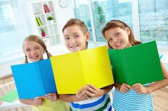 Niños sonrientes con libros abiertos