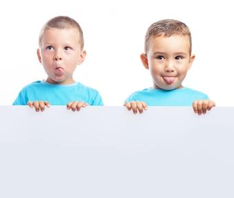 Niños sujetando una pancarta en blanco mientras ponen caras raras