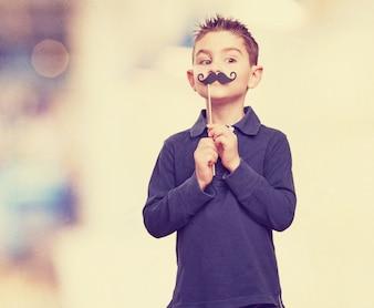 Niño con un bigote falso