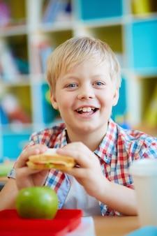 Niño feliz comiendo un bocadillo