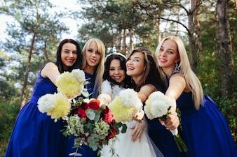 Novia con damas de honor sosteniendo ramos posando