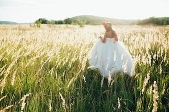 Novia en un hermoso vestido largo posando en el jardín.