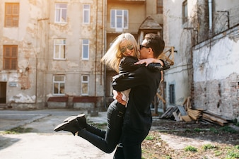 Novia saltando encima de su novio mientra la sujeta en el aire