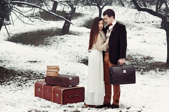 Novia y el novio con la vieja maleta de pie en el parque de invierno