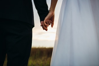 Novia y el novio se celebran entre sí las manos de pie en el campo