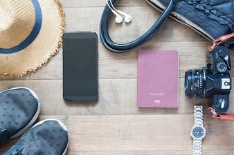 Objetos de viaje y accesorios con dispositivo móvil sobre fondo de madera, plano