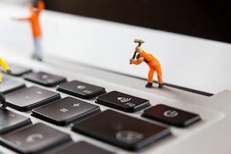 Obreros en miniatura que reparan un teclado portátil