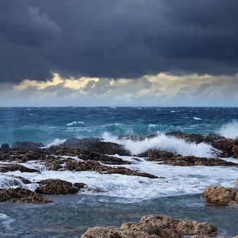 Ola de mar rompiendo contra la costa roca