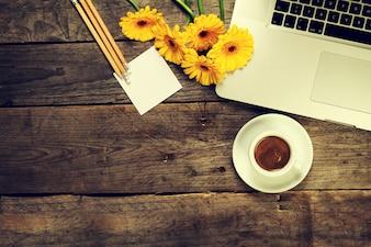 Ordenador portátil con una taza de café y flores