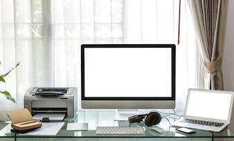 Ordenador, portátil e impresora sobre un escritorio