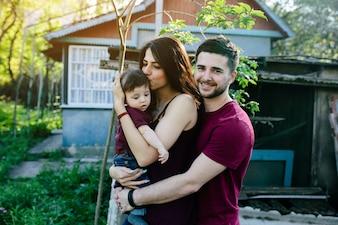 Padre abrazando a su mujer y esta con un bebe en brazos