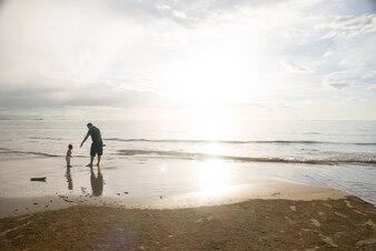 Padre jugando con su hijo en la orilla