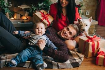 Padre sujetando a su bebé en alto mientras su mujer los mira