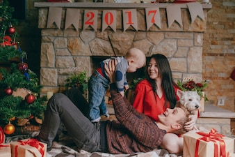 Padre tumbado en el suelo con una chimenea de fondo mientras levanta a su bebé en alto y la madre los mira sonriendo