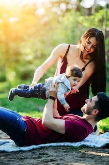 Padre tumbado en un parque con su bebé en alto y su madre ayudandole