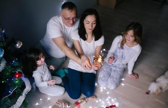Padres con los niños en el árbol de Navidad