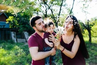 Padres con un bebé en brazos soplando dientes de león