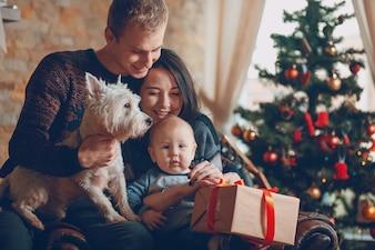 Padres con un perro y un bebé con un árbol de navidad de fondo
